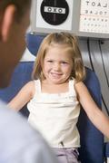 Optometrist in exam room with young girl in chair smiling Stock Photos