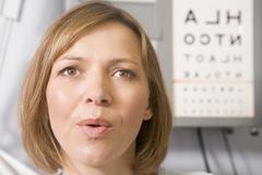 Woman in optometrist's exam room taking deep breath Stock Photos