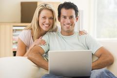 Couple in living room using laptop smiling - stock photo