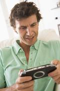 Man in living room playing handheld videogame smiling - stock photo