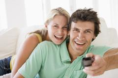 Couple in living room holding remote control smiling - stock photo