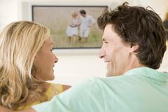 Couple in living room watching television smiling Stock Photos