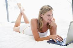 Woman lying in bed with laptop smiling - stock photo