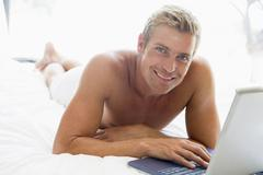 Man lying in bed with laptop smiling Stock Photos