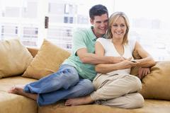 Couple in living room with remote control smiling - stock photo