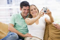 Couple in living room with digital camera smiling - stock photo