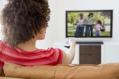 Woman in living room watching television - stock photo