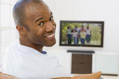 Man in living room watching television smiling - stock photo