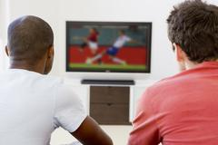 Two men in living room watching television Stock Photos