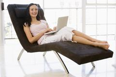 Woman sitting in chair using laptop smiling - stock photo