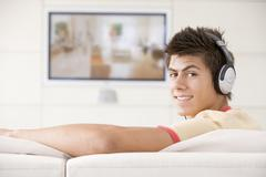 Man in living room watching television and wearing headphones Stock Photos