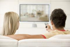 Couple in living room watching television - stock photo