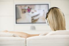 Woman in living room watching television and wearing headphones Stock Photos
