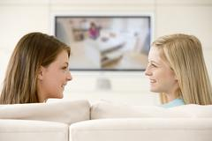 Two women in living room watching television smiling - stock photo