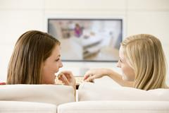 Two women in living room watching television eating chocolates smiling - stock photo