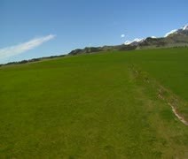 Wobbly aerial shot with green field and snow mountains in distance Stock Footage
