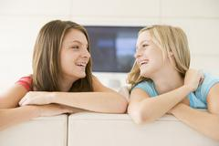 Two women in living room smiling - stock photo