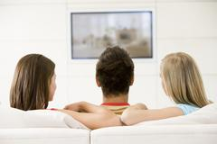 Three friends in living room watching television - stock photo