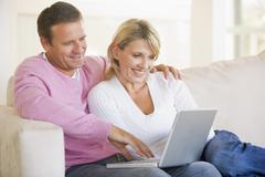 Couple in living room using laptop and smiling - stock photo