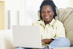 Woman in living room using laptop and smiling - stock photo