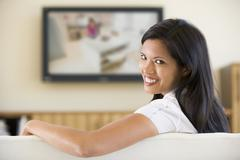 Woman in living room watching television smiling Kuvituskuvat