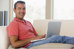 Man in living room using laptop smiling - stock photo