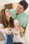 Couple in living room with remote control smiling Stock Photos