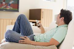 Man in living room watching television Stock Photos
