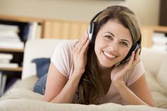 Woman in living room listening to headphones smiling Stock Photos