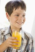 Young boy indoors drinking orange juice smiling - stock photo