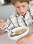 Young boy in kitchen eating soup Stock Photos