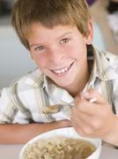 Young boy in kitchen eating soup and smiling Stock Photos