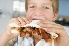 Young boy in kitchen eating bacon sandwich - stock photo