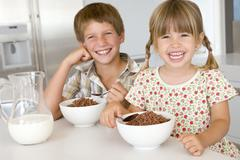 Two young children in kitchen eating cereal smiling Stock Photos