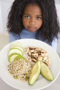 Young girl in kitchen eating rice fruit and nuts - stock photo