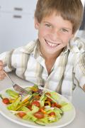 Young boy in kitchen eating salad smiling Stock Photos
