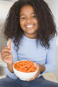Young girl in kitchen eating carrot sticks smiling Stock Photos