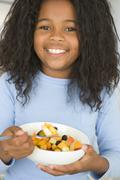 Young girl in kitchen eating bowl of fruit smiling Stock Photos