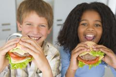 Two young children in kitchen eating cheeseburgers smiling - stock photo