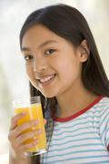 Young girl indoors drinking orange juice smiling Stock Photos