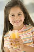 Stock Photo of Young girl indoors drinking orange juice smiling