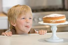 Young boy in kitchen looking at cake on counter - stock photo