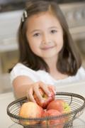 Young girl in kitchen getting apple off counter smiling Stock Photos
