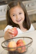 Young girl in kitchen getting apple off counter smiling - stock photo