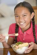 Young girl in dining room eating Chinese food smiling Stock Photos