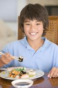 Young boy in dining room eating chinese food smiling Stock Photos