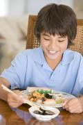 Nuori poika ruokasalissa syöminen kiinalaista ruokaa hymyillen Kuvituskuvat