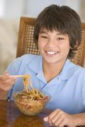 Young boy in dining room eating chinese food smiling - stock photo