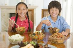Two young children eating chinese food in dining room smiling Stock Photos