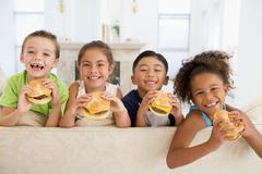 Four young children eating cheeseburgers in living room smiling Stock Photos